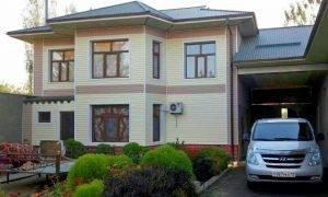 Двухэтажный дом с белым сайдингом